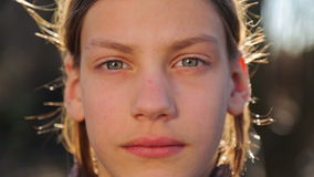 The teenager closes a hand lens of the camera. Portrait of a boy close-up, open and close the camera. stock footage