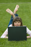 Teenager with computer on the grass royalty free stock image