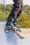 Teenager con i pattini di rullo che eseguono un'acrobazia su una mezza rampa del tubo fotografie stock