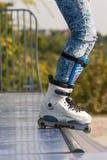 Teenager con i pattini di rullo che iniziano un'acrobazia su una mezza rampa del tubo fotografie stock