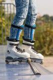 Teenager con i pattini di rullo pronti per un'acrobazia su una mezza rampa del tubo immagini stock