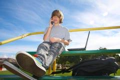 Teenager con il telefono delle cellule sui bleachers Fotografia Stock Libera da Diritti