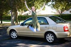Teenager con l'automobile salta per la gioia Fotografia Stock