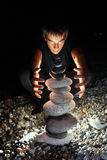 Teenager conjuring near pyramid from pebble. Teenager boy conjuring near pyramid from pebble on stony seacoast at night Stock Photography