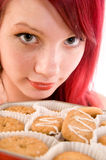 Teenager with cookies. Close up of red headed teenage girl with face next to freshly baked cookies stock photo