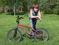 The teenager costs on a  lawn and leans again. The teenager costs on a solar lawn and leans against a bicycle Stock Photo