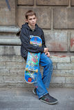 The teenager costs at a wall with a skateboard Royalty Free Stock Photo