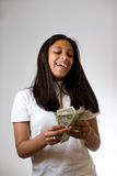 Teenager counting money. A young girl counting money. Hispanic/Latin, happy.  Can denote babysitting and odd jobs, success, materialism.  Looking at the money Royalty Free Stock Image