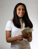 Teenager counting money. A young girl counting money. Hispanic/Latin, happy.  Looking at the camera confidently and joyful Royalty Free Stock Photos
