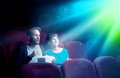 Teenager couple watching movie. Teenager couple cuddling and watching the climax part of the movie Royalty Free Stock Photos