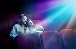Teenager couple watching movie. Teenager couple cuddling and watching the climax part of the movie Stock Photo
