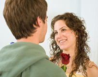 Teenager couple romance. Teenager boy giving rose to girlfriend Stock Photography