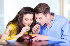 Teenager couple sharing cocktail. Sitting at table in a coffee bar stock image