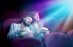 Teenager couple watching movie. Teenager couple cuddling and watching the climax part of the movie Stock Images