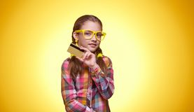 Beautiful teen girl with credit card over yellow background stock photo