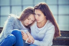 Teenager cries, her girlfriend sympathizes. The Female Teen is Crying because of Teenage Problems, and Her Friend Looks Sympathetically at Her, Sitting on the Royalty Free Stock Photos