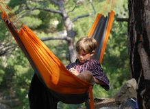 Teenager. Crimea trekking. Relax in a hammock. Teenager reading an e-book Royalty Free Stock Photo