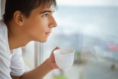 Teenager with cup in hand looking out of window Royalty Free Stock Image