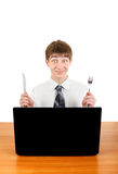 Teenager with Cutlery behind Laptop Stock Photo