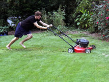 Teenager cutting grass Stock Photos
