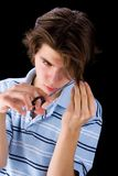 Teenager cutting hair. Portrait of handsome male teenager cutting own hair, isolated on black background royalty free stock photo