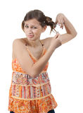 Teenager cutting hair with scissor over white. Girl in orange dress cutting hair with scissor over white background royalty free stock photos