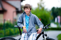 Teenager cycling. Teenager standing near a bike Royalty Free Stock Image