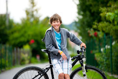 Teenager cycling. Teenager standing near a bike Stock Image