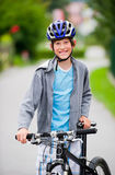 Teenager cycling. Teenager standing near a bike, wearing a helmet and smiling Stock Photography
