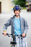 Teenager cycling. Teenager standing near a bike, wearing a helmet and smiling Royalty Free Stock Photo