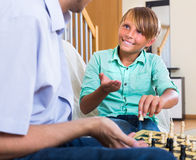 Teenager with dad having chess game Royalty Free Stock Images