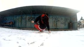 Teenager dancing breakdance in snow, slowmotion stock video footage