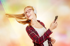 Teenager dancing to the music comming from her headphones Royalty Free Stock Photos
