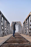 Teenager in depression sitting on the bridge at the sunset. Royalty Free Stock Images