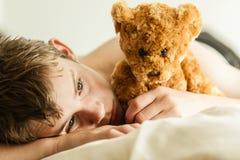 Teenager, der auf Bett mit Brown Teddy Bear sich anschmiegt lizenzfreie stockbilder