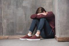 Teenager, der auf Boden mit Kopf in den Händen sitzt Stockfotografie