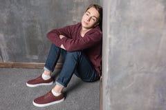 Teenager, der auf Boden sitzt und weg schaut Stockfotografie