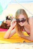 Teenager, der auf dem Strand sich bräunt Stockbild
