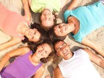 Teenager, der auf einem Strand in einem Kreis liegt Stockbilder