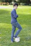 Teenager, der auf Fußball-Kugel steht stockbilder