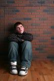 Teenager, der auf Fußboden mit den Armen auf Knien sitzt Lizenzfreies Stockfoto