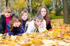 Teenager, der auf herbstlichen Blättern liegt Lizenzfreie Stockfotos