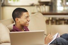 Teenager, der auf Sofa At Home Doing Homework verwendet Laptop-Computer sitzt, während, fernsehend Stockfotos