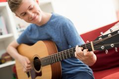 Teenager, der auf Sofa At Home Playing Guitar sitzt Stockbilder