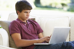 Teenager, der auf Sofa At Home Using Laptop sich entspannt Stockbilder