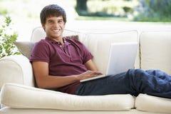 Teenager, der auf Sofa At Home Using Laptop sich entspannt Stockfotografie