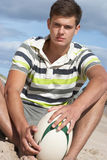 Teenager, der auf Strand-Holding-Rugby-Kugel sitzt Stockbild