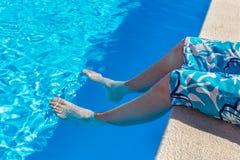 Teenager, der bloße Beine im blauen Swimmingpool hält Stockfoto
