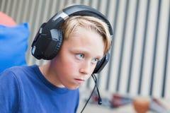 Teenager, der Computerspiele auf PC spielt Stockbild