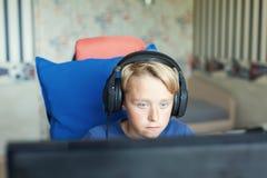 Teenager, der Computerspiele auf PC spielt Stockbilder